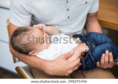High angle view of father carrying sleeping baby at home