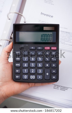 High angle view of female accountant holding calculator at desk in office
