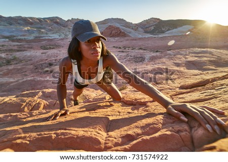 High angle view of female african american hiker climbing rock at Valley of Fire in nevada desert