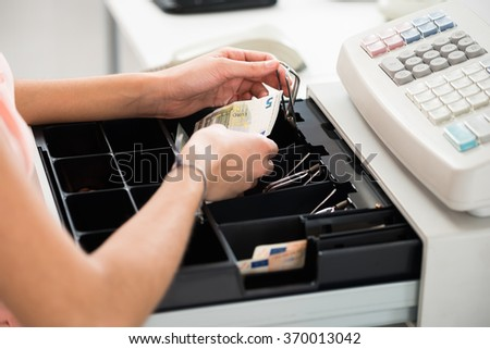 High angle view of female cashier searching for change in cash register drawer at supermarket - stock photo