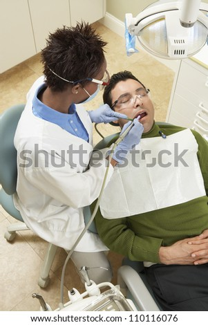 High angle view of female dentist treating male patient at clinic - stock photo