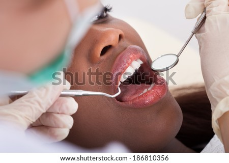 High angle view of female patient being examined by dentist in clinic - stock photo