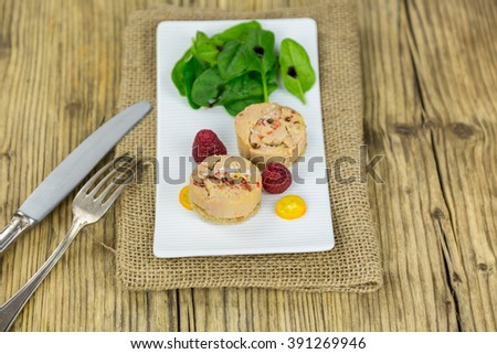 High Angle View of Goose Liver Pate Garnished with Baby Spinach Salad and Raspberries Served on Rectangular Plate, Burlap Placemat and Rustic Wooden Table with Knife and Fork - stock photo
