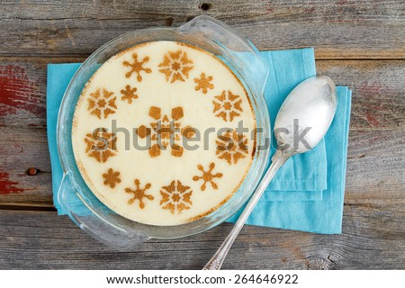 High Angle View of Gourmet Semolina Dessert with Milk Served on a Glass Bowl on Top of a Rustic Wooden Table with Napkin and Spoon. - stock photo