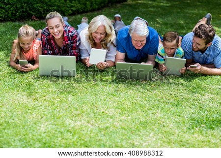 High angle view of happy family with technologies lying in yard - stock photo