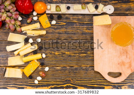 High Angle View of Ingredients for Cheese Board - Rustic Wooden Table with Cutting Board and Variety of Cheeses and Fruits with Copy Space in Center of Image - stock photo