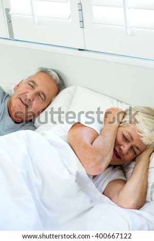 High angle view of irritated senior woman sleeping by snoring man on bed at home - stock photo