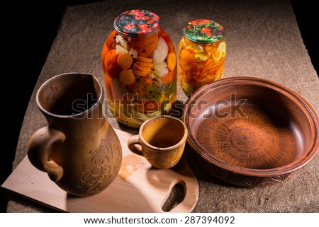 High Angle View of Jars of Pickled Vegetable Preserves on Table Surface Next to Carved Wooden Handicrafts - Wood Pitcher, Cup, Bowl and Wooden Cutting Board with Copy Space - stock photo
