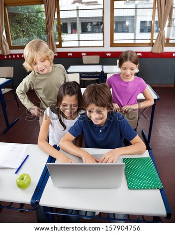 High angle view of little schoolchildren using laptop at desk in classroom - stock photo