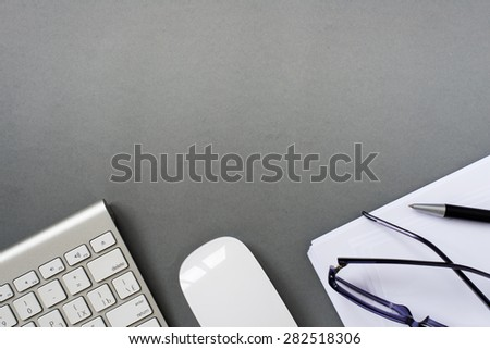 High Angle View of Mac Computer Keyboard and Mouse with Paper, Pen and Eyeglasses on Grey Desk with Ample Copy Space - stock photo