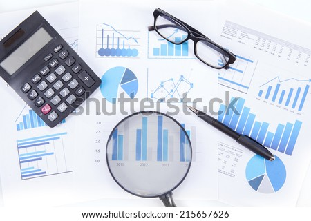 High angle view of magnifying glass with business chart, calculator, glasses, and pen
