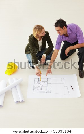 high angle view of male architect and woman examining blueprints. Copy space - stock photo