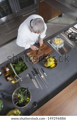High angle view of male chef chopping kiwi on board at commercial kitchen counter - stock photo