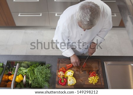 High angle view of male chef dicing red and yellow bell peppers in commercial kitchen - stock photo