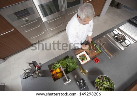 High angle view of male chef slicing cucumber on board at commercial kitchen counter - stock photo