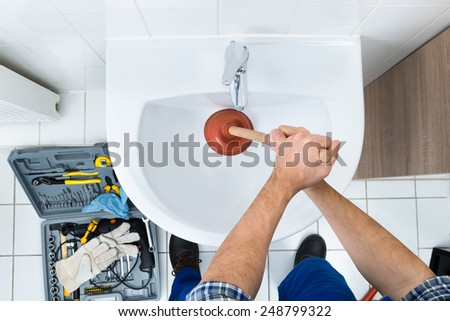 High Angle View Of Male Plumber Using Plunger In Bathroom Sink - stock photo