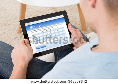 High angle view of man filling survey form online on digital tablet at home