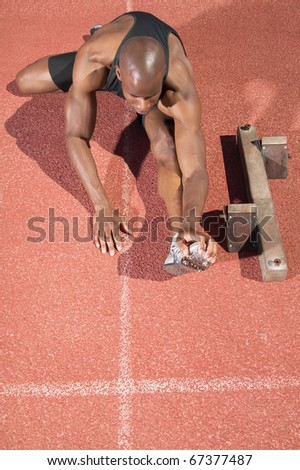 High angle view of man stretching on track