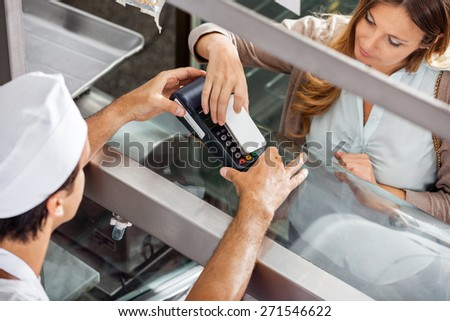 High angle view of mature female customer paying through smartphone at butchery - stock photo