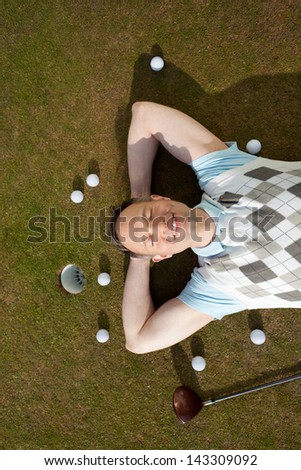 High angle view of mature man with balls and club lying on grass at golf course - stock photo