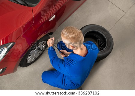 High Angle View Of Mechanic Changing Tire In Garage With Wrench - stock photo