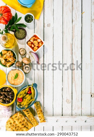 High Angle View of Mediterranean Appetizers Spread Out on Rustic White Wooden Picnic Table with Copy Space - stock photo