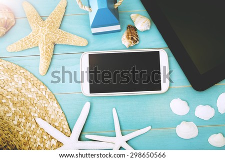 High Angle View of Mobile Gadgets on Top of Light Blue Table with Starfish, Sea Shells and Beach Hat