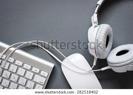 High Angle View of Modern White Audio Headphones with Cord, Mac Computer Keyboard and Mouse on Grey Desk Background with Copy Space - stock photo