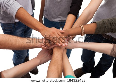 High angle view of multiethnic college students stacking hands against white background - stock photo