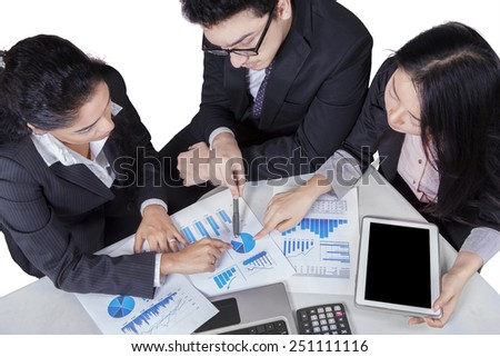 High angle view of multiracial business team in a business meeting pointing at a pie chart on paperwork - stock photo