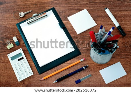 High Angle View of Office or School Supplies Arranged Neatly Around Clipboard with Blank Page on Wooden Desk Surface - stock photo