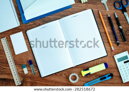 High Angle View of Office or School Supplies Neatly Organized Around Open Note Book with Blank Page on Wooden Desk Top - stock photo