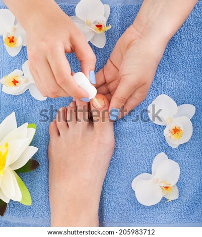 High angle view of pedicurist applying plain varnish on woman's toenail at beauty salon - stock photo