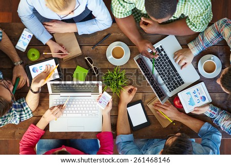 High angle view of people communicating at table with their devices - stock photo
