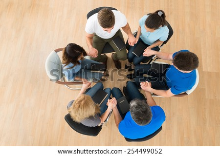 High Angle View Of People Holding Each Others Hand Praying Together - stock photo