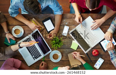 High angle view of people meeting at table and working with laptops and touchpads - stock photo