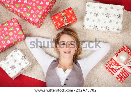 High Angle View of Pretty Young Woman Lying on the Floor with Both Hands on the Back of the Head While Looking at the Camera, Surrounded by Various Christmas Gift Boxes. - stock photo
