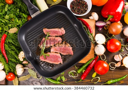 High Angle View of Rare Seasoned Sliced Beef Sizzling in Hot Frying Pan Surrounded by Bounty of Ingredients - Colorful Vegetables and Fresh Herbs and Spices