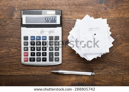 High Angle View Of Receipts With Calculator And Pen On Table - stock photo