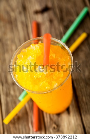 High Angle View of Refreshing and Cool Orange Frozen Slush Drink in Plastic Cup Served on Rustic Wooden Table with Collection of Colorful Drinking Straws - stock photo