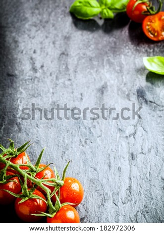 High angle view of risp of tomatoes on slate background with copyspace - stock photo