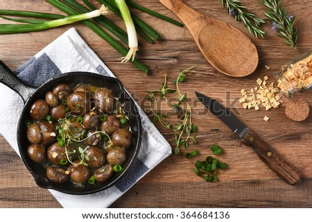 high angle view of sautéed mushroom caps in a cast iron skillet surrounded by ingredients and utensils. Horizontal on a rustic kitchen table. - stock photo
