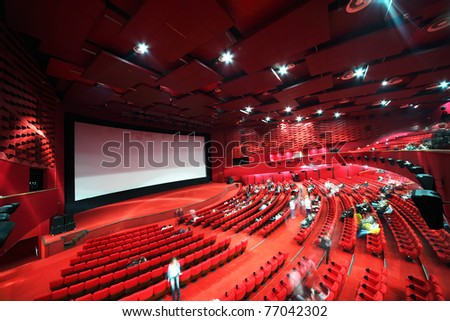 High-angle view of screen and rows of comfortable red chairs filled by people in illuminate red room cinema - stock photo