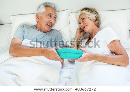 High angle view of senior man and woman holding gift box on bed at home - stock photo