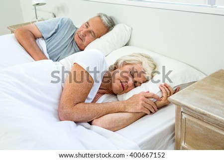 High angle view of senior man and woman sleeping on bed at home - stock photo
