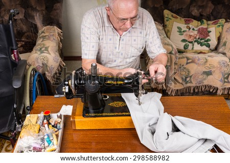 High Angle View of Senior Man Mending Pants with Old Fashioned Manual Sewing Machine at Home in Living Room - stock photo