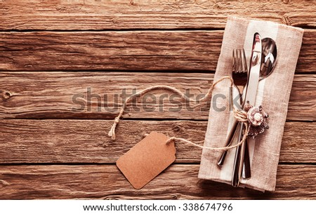 High Angle View of Set of Silver Cutlery Tied with String and Blank Tag on Natural Colored Napkin on Rustic Wooden Table with Copy Space - stock photo