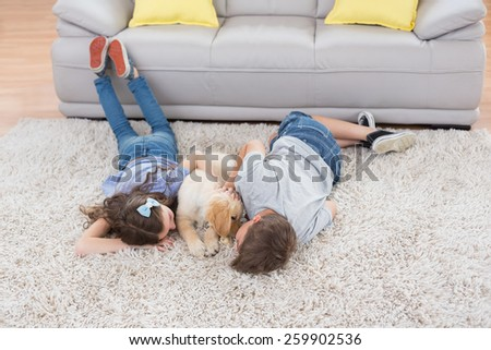 High angle view of siblings with dog lying on rug