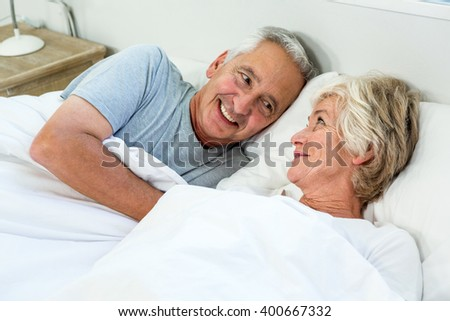 High angle view of smiling senior couple relaxing on bed at home - stock photo