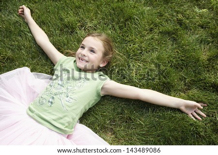High angle view of smiling young girl with arms outstretched lying on grass - stock photo